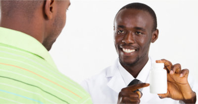 pharmacist showing medicine bottle to his customer
